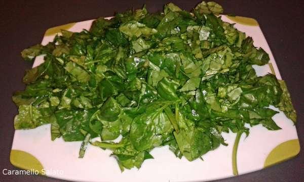 Lavare gli spinaci, disporli su un tagliere e tagliarli grossolanamente