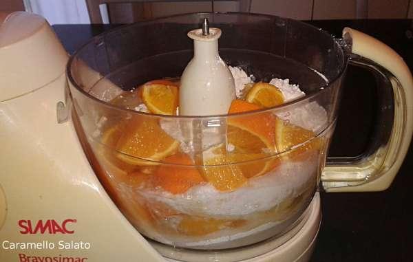 Lavare bene l'arancia, tagliarla a pezzetti e privarla dei semi. Inserire nel robot da cucina tutti gli ingredienti