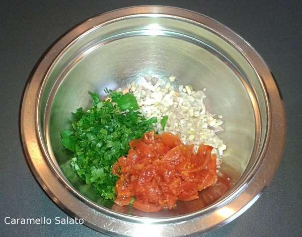 In una ciotola radunare il trito di prezzemolo, i pomodorini e il trito di scalogno, aglio e peperoncino