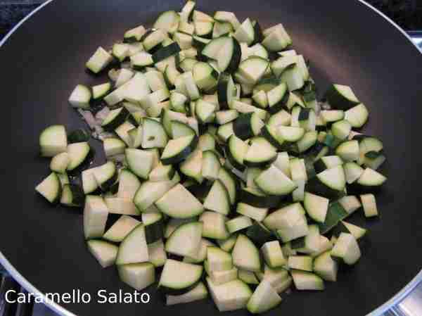 Lavare, spuntare e tagliare a dadini le zucchine. Aggiungerle allo scalogno. Salare e pepare e lasciar cuocere una decina di minuti