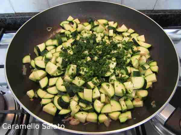 Tagliare finemente il prezzemolo, lavare ed asciugare le foglie di basilico ed aggiungerle alle zucchine e mescolare