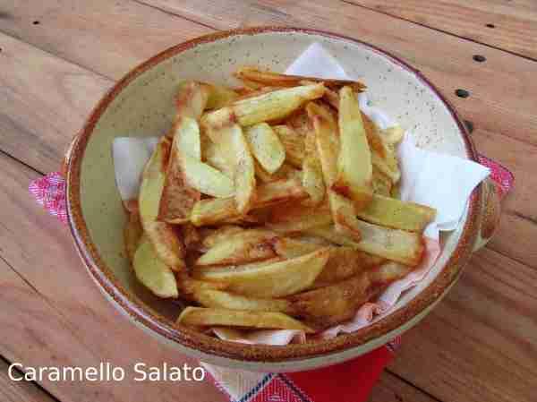 Quando le patate sono dorate sollevarle con la schiumarola e metterle in una ciotola sopra un foglio di carta assorbente. Aggiungere sale e pepe e mescolare