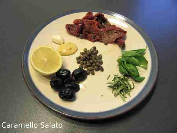 Spellare l'aglio, lavare il basilico e il rosmarino, prelevare gli aghi, sgocciolare i pomodori secchi e sciacquare dal sale i capperi, snocciolare le olive