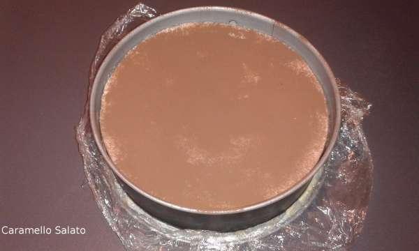 Una volta rassodato estrarre il dolce, versare il cacao amaro facendolo passare attraverso un colino, passare la lama del coltello tutto intorno al cerchio, aprire il cerchio e disporre il semifreddo sul piatto di portata