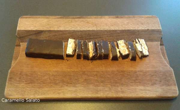 Su un tagliere iniziare a tritare grossolanamente il torrone ricoperto di cioccolato